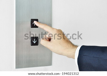 Businessman hand touching going up sign on lift control panel - stock photo