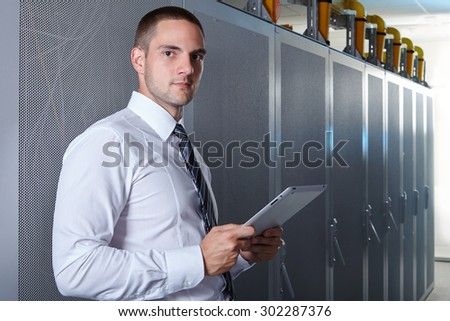 businessman hand using tablet computer in modern server room - stock photo