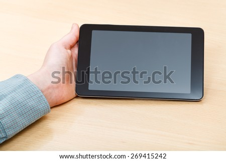 businessman hand with tablet PC with black screen at office table - stock photo