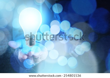 Businessman hand working with 3d light bulb of leadership concept and bokeh exposure - stock photo