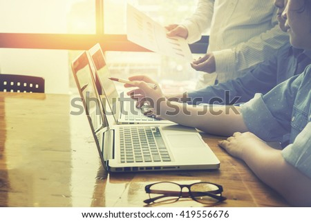 businessman hand working with new modern computer and business strategy as concept,Young creative team working together, People Meeting Design Ideas Concept,vintage color,selective focus - stock photo