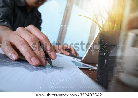 businessman hand working with new modern computer and business strategy documents and digital layers with green plant and glass of water foreground on wooden desk in office - stock photo