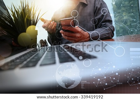 businessman hand working with new modern computer and business strategy documents digital layers with green plant foreground on wooden desk in office - stock photo