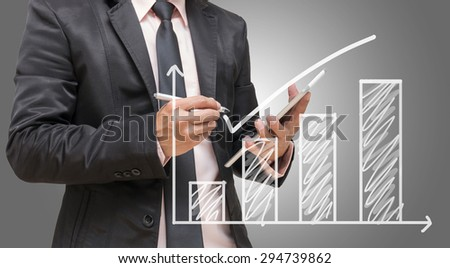 Businessman hand writing a graph on gray background, Business investment concept - stock photo