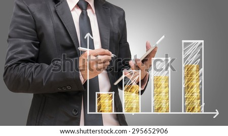 Businessman hand writing a graph with gold coin on gray background, Business investment concept - stock photo