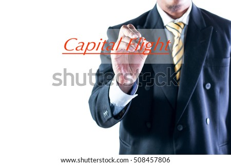 Businessman hand writing Capital Flight on transparent wipe board.