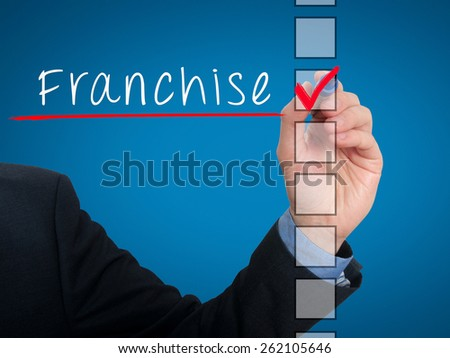 Businessman hand writing Franchise and check listing task. Isolated on blue background. Stock photo