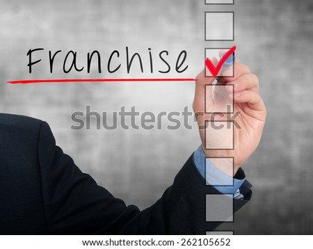 Businessman hand writing Franchise and check listing task. Isolated on grey background. Stock photo - stock photo