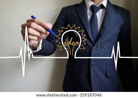 businessman hand writing heartbeat with light bulb idea , business idea , business concept ,Innovation concept - stock photo