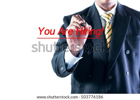 Businessman hand writing You Are Hiring on a transparent wipe board.