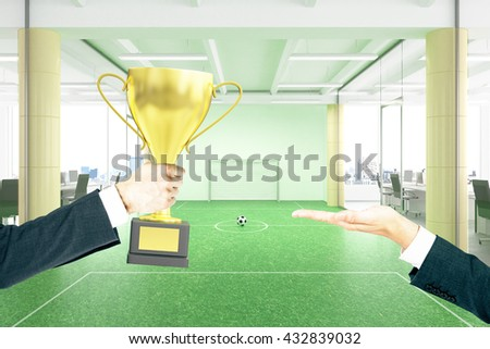 Businessman handing golden cup trophy to another man with football field in office in the background. Mock up, 3D Rendering - stock photo