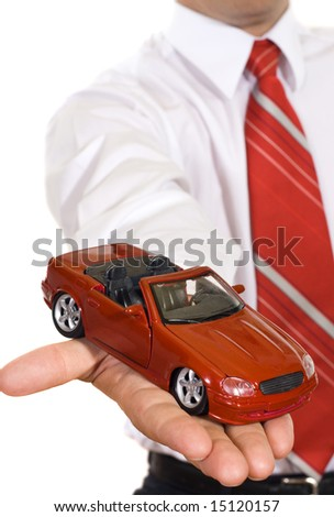 Businessman handing over a new red toy car - isolated - stock photo
