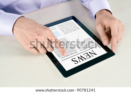 Businessman hands are pointing on contemporary digital tablet pc with latest news lying on table. - stock photo