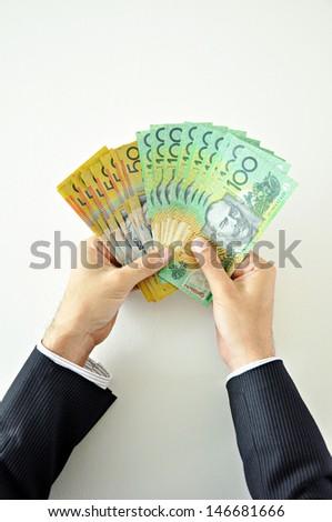 Businessman hands holding money - Australian Dollar banknotes - stock photo