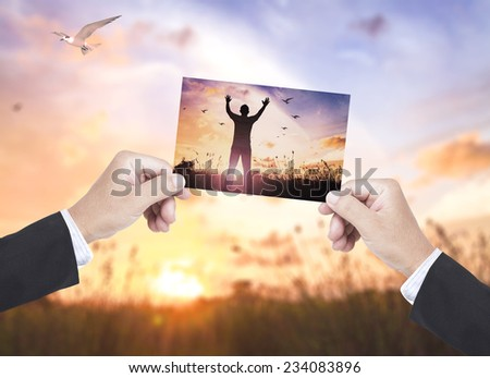 Businessman hands holding picture silhouette of man with hands raised compare with the actual location. - stock photo