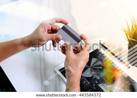 Businessman hands holding plastic credit card and using digital tablet and laptop computer with smart phone. Online shopping concept.On marble table, Sun flare effect - stock photo