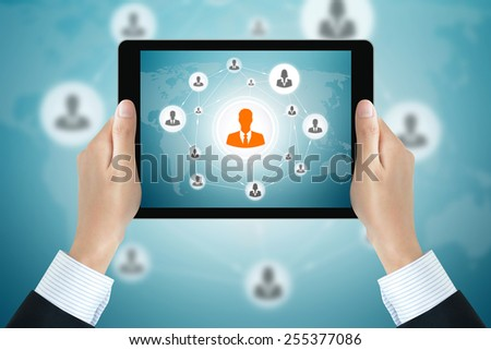 Businessman hands holding tablet pc with businesspeople icons linked as network on the screen - online business & social network concepts - stock photo