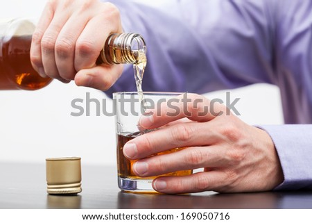 Businessman hands pouring alcohol into glass - alcoholism - stock photo