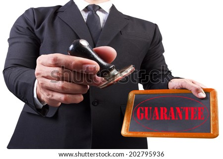 businessman hands put the stamp wood blackboard red guarantee word stamp on white background with clipping path - stock photo