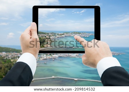 Businessman hands tablet taking pictures beach and sea on cloud