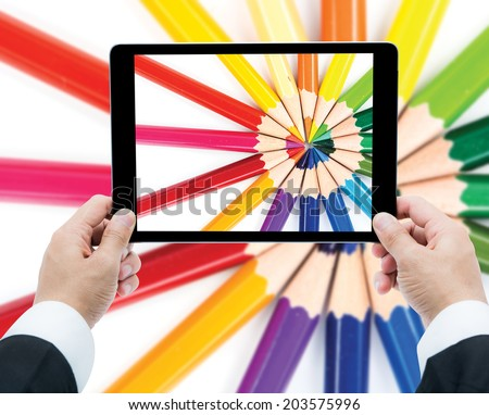Businessman hands tablet taking pictures close up color pencils on a white background - stock photo