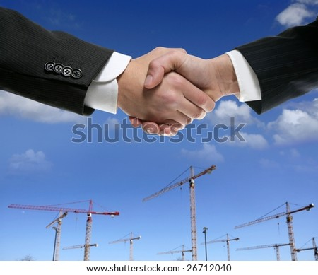 Businessman handshake in construction crane area over blue sky [Photo Illustration]