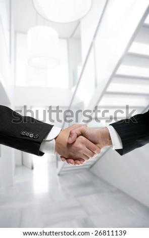 Businessman handshake on modern white stairway office [Photo Illustration] - stock photo