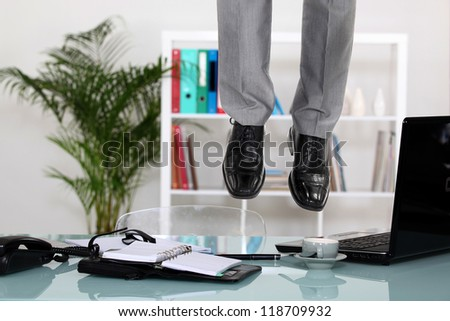 Businessman hanging from ceiling - stock photo
