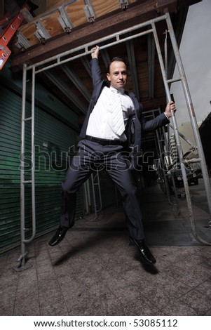 Businessman hanging from scaffolding