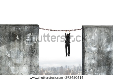 Businessman hanging on rusty chain connected two high dirty concrete walls, with cityscape background. - stock photo