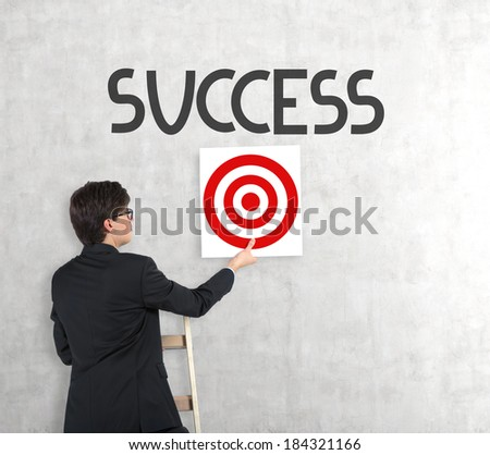 Businessman hanging up the target 2 - stock photo