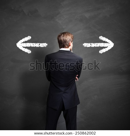 businessman has to decide between two directions - stock photo