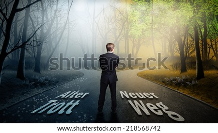 businessman has to decide which direction is better. On the road is stated in German old routine to the left and new way to the right. - stock photo