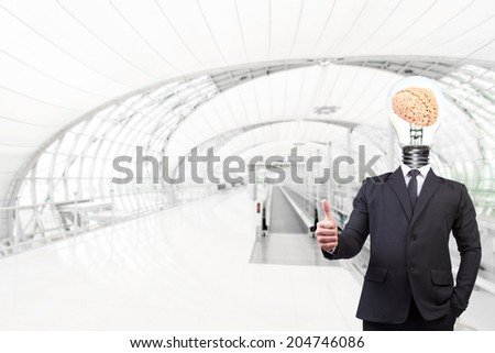 businessman have head brain inside a light bulb thumb up at futuristic airport interior with concept of real estate and engineering for success business creativity - stock photo