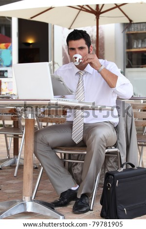 Businessman having a coffee break on a terrace - stock photo