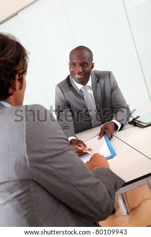 Businessman having client signing contract - stock photo