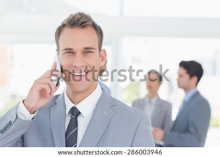 Businessman having phone call while his colleagues discussing in the office - stock photo