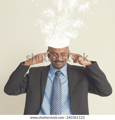 Businessman head burnout, smoke coming out from head. - stock photo