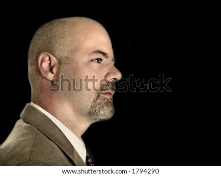 businessman headshot from the side, looking to the right of the frame. - stock photo