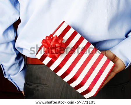 Businessman hiding a nice wrapped gift - stock photo
