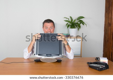 Businessman hiding behind computer with smiley face - stock photo