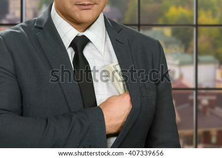 Businessman hiding dollars into jacket. Man with cash at daytime. Mind every step. Profitable deal gone well. - stock photo