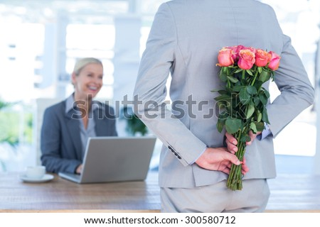 Businessman hiding flowers behind back for colleague in an office - stock photo