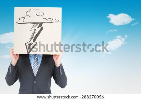 Businessman hiding head with a box against blue sky - stock photo