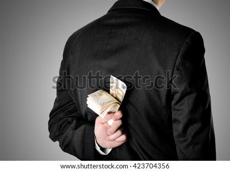 Businessman hinding fifty euro bank notes behind his back - stock photo