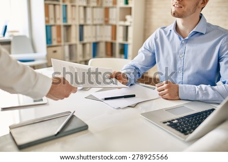 Businessman his colleague giving contract to read and sign - stock photo