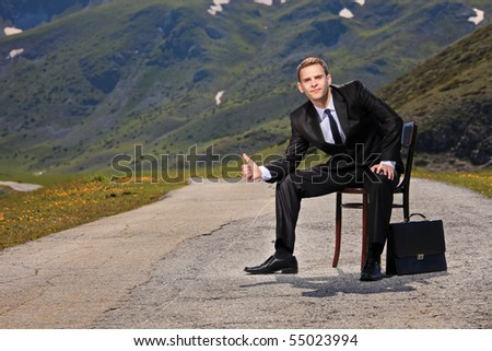 Businessman hitchhiking on a highway - stock photo