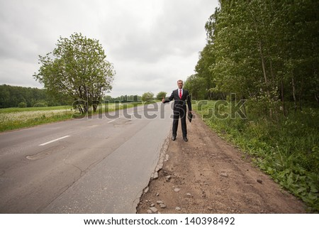 Businessman hitchhiking on a road - stock photo