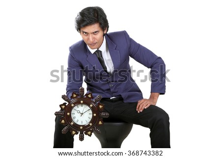 Businessman hold clock, handsome young business man  wear elegant suit and tie isolated over white background - stock photo