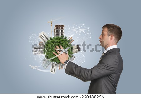 Businessman hold Earth with buildings